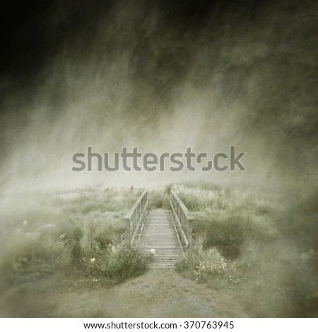Deserted old wooden footbridge in a lonely, misty landscape captured using long exposure, bokeh and other effects with some areas blurred to create a surreal and dreamlike effect.
