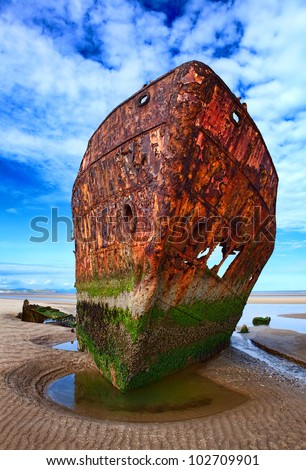 Deserted rusty ship on the coast of a ocean - stock photo