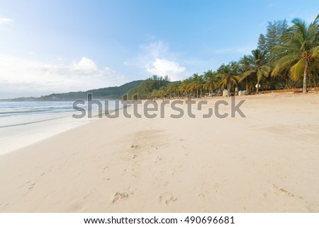 Deserted sandy tropical beach on Phuket island during low tourist and rainy season at summer in Thailand. Kamala beach.