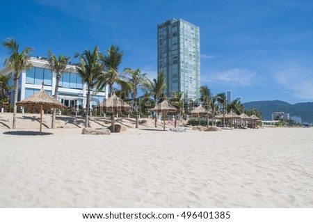deserted tropical beach with white sand and straw umbrellas