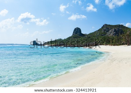 Deserted tropical island beach with clear blue water and rocky mountain, Izena Island, Okinawa, Japan - stock photo