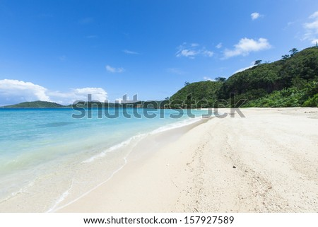 Deserted tropical paradise beach with clear blue lagoon water and white coral sand, Iriomote Island of Yaeyama Islands, Okinawa, Japan - stock photo