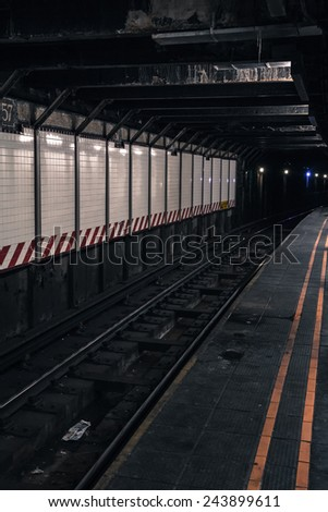 Deserted underground subway platform and tracks in New York City. Processed with added grain - stock photo