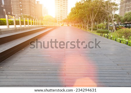Deserted walkway and bench steps in an urban park surrounded by high-rise commercial buildings , low angle view