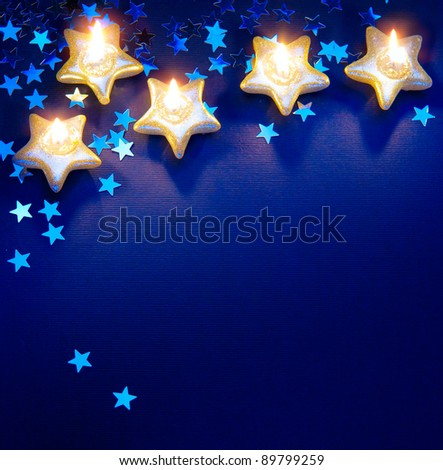Design a background for the Christmas greetings card with candles on a blue background