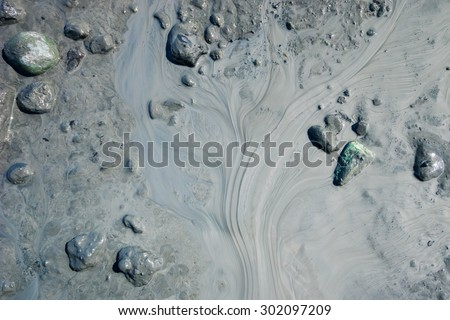 Design and gradation of mud and silt flow in slow moving stream. - stock photo