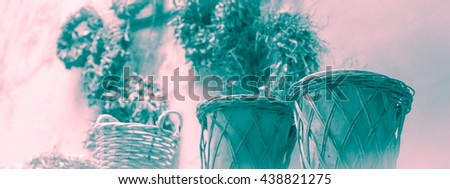 Design and style banner - Rustic garden pots and old wicker baskets against grunge wall - pale teal blue and rose quartz pink tinted black and white photograph with blurred light vintage filter effect - stock photo