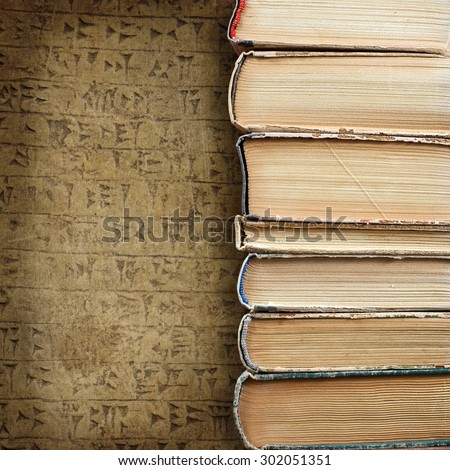 Design concept of wisdom and knowledge power - close up view on stacked old books placed on grunge background with Sumerian cuneiform theme and blank place for your text or figure - stock photo