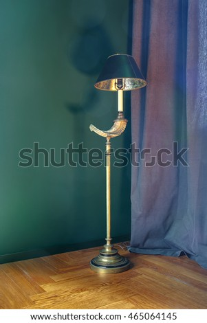 Design golden metal glowing lamp with turquoise shade on the background of the turquoise wall and curtain. Lamp drops shadow on the wall. On the floor there is a parquet. Indoors. Vertical.
