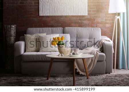 Design interior of living room with grey sofa and bouquet of flowers on table - stock photo