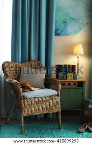 Design interior with wicker armchair and wooden nightstand indoors - stock photo