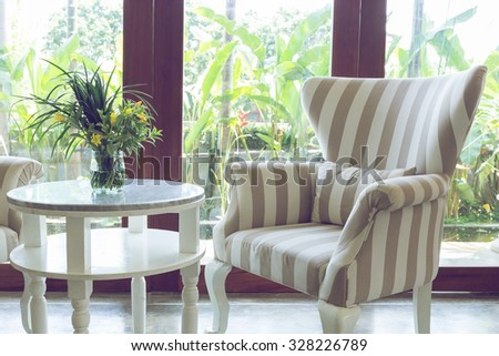 design of interior living room with sofa furniture with mirror window and green garden background - stock photo
