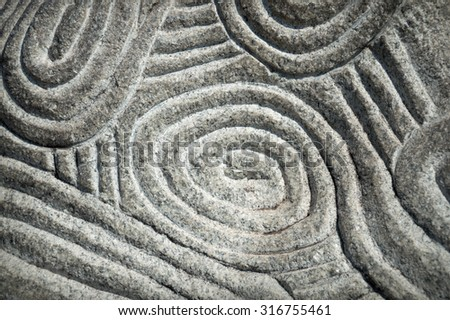 Design of naive round ethnic pagan intricacy motif in deep convex volume rough bumpy weathered furrow notch coarse wall slab. Close-up view with space for text on dark leaden stripes