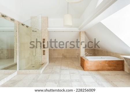 Design of rock bathroom with wooden bathtub - stock photo