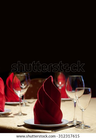 Design restaurant menu template. Served table in a restaurant with a yellow tablecloth, red napkins, wine glasses and cutlery. Copy space, black background - stock photo
