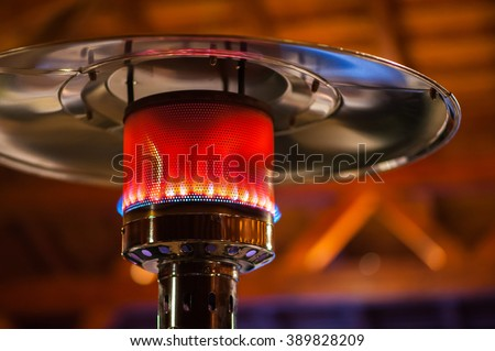 Design stainless steel metal gas burning indoor patio heater with blurred enteriour background - stock photo