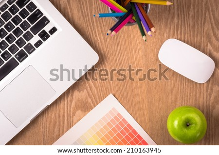 Design table with laptop, color pencils and palette paper. View from above - stock photo