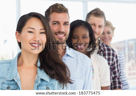 Design team standing in a row smiling at camera in creative office - stock photo