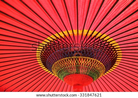 Design underneath the red Japanese umbrella - stock photo