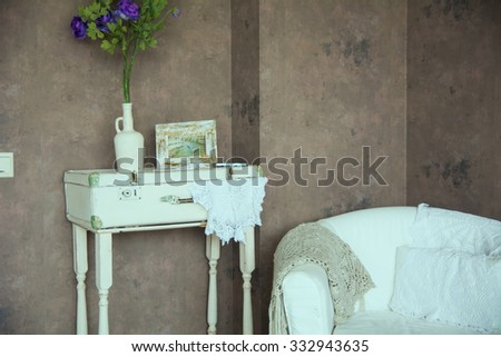 Design vintage interior with flowers in the bottle and the image in the frame. Aged chair against the wall - stock photo