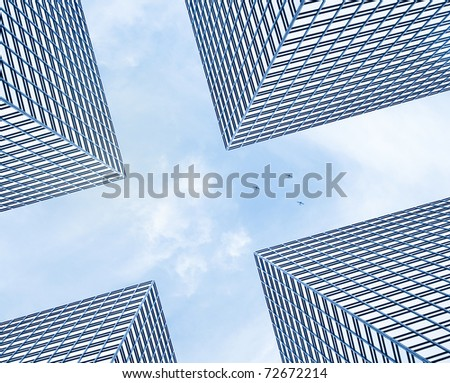Designed futuristic background - three small private planes rising up above four giant modern business buildings in front of cloudy blue sky - stock photo