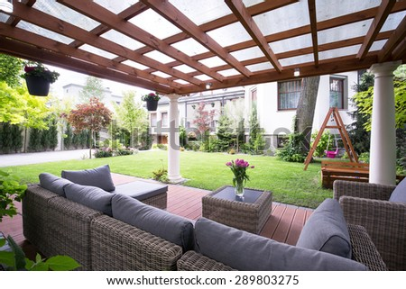 Designed modern arbour with comfortable garden furniture - stock photo