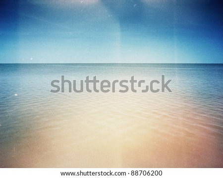Designed retro photo. Sunny day on the beach. Grain, dust, colors added as vintage effect. - stock photo