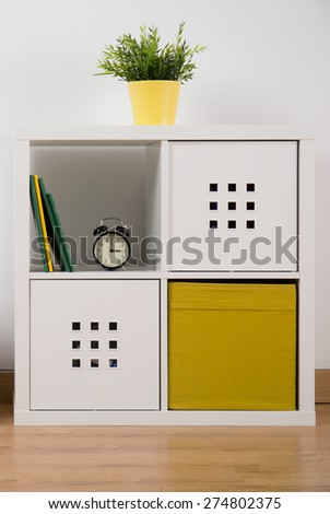 Designed white and yellow cupboard in teen room - stock photo