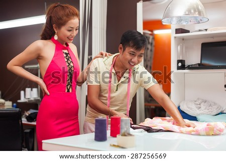 designer asian man tailor shop working on table with woman customer fashion dress clothes