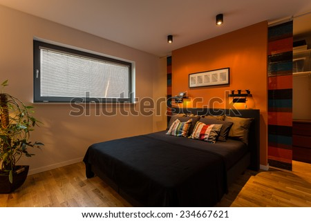 Designer bedroom with orange wall and color cushions - stock photo