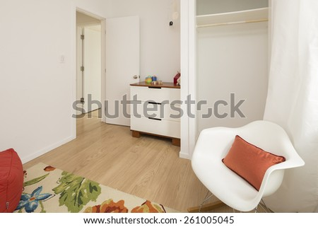 Designer chair in Children bedroom with white chest. - stock photo