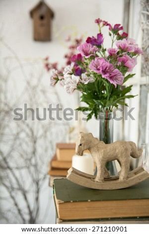 Designer composition with artificial flowers. Toy horse with books tree branches and birdhouse - stock photo