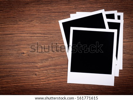 Designer concept - blank photo frames for your photos on wooden background