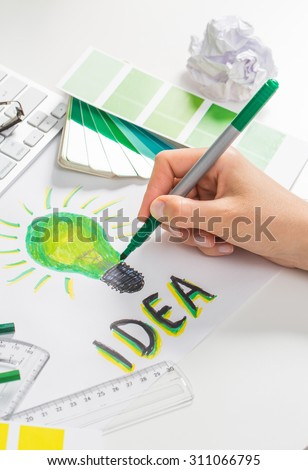 Designer drawing a green light bulb. Brainstorming and inspiration cocnept. - stock photo