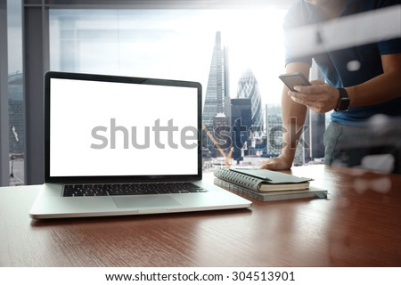 designer hand working and smart phone and blank screen laptop on wooden desk in office with london city background - stock photo