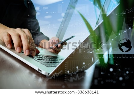 designer hand working and smart phone and laptop and digital business layers with green plant foreground on wooden desk in office - stock photo
