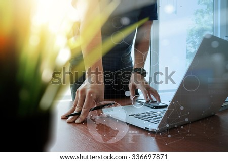 designer hand working laptop with green plant foreground and digital social diagram layers on wooden desk in office - stock photo