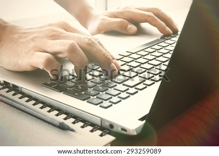 designer hand working with digital tablet and laptop and notebook stack and eye glass on wooden desk in office - stock photo