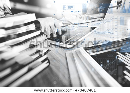designer hand working with digital tablet and laptop computer and book stack and eye glass on wooden desk . virtual screen , black white