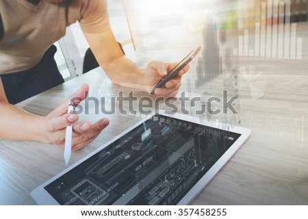 Designer hand working with digital tablet computer and smart phone on wooden desk as responsive web design concept - stock photo