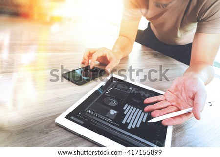 Designer hand working with digital tablet computer and smart phone on wooden desk as responsive web design concept