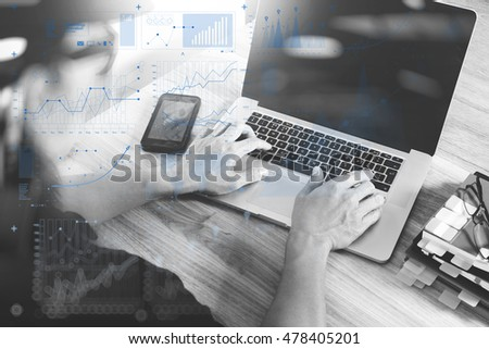 Designer hand working with laptop computer on wooden desk as responsive web design concept. virtual screen , black white