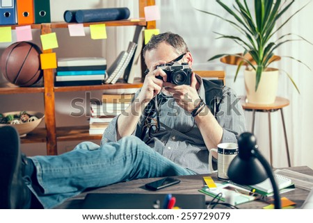Designer in his office holding old camera - stock photo