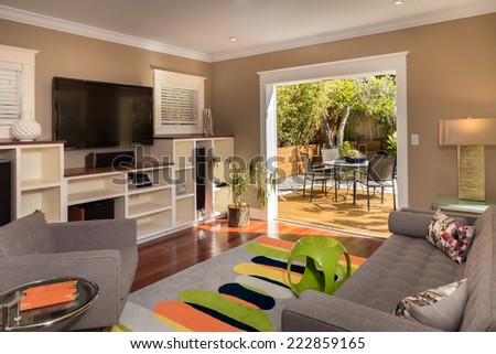 Designer Living room leading to outdoors with grey couch and white furnishing. - stock photo