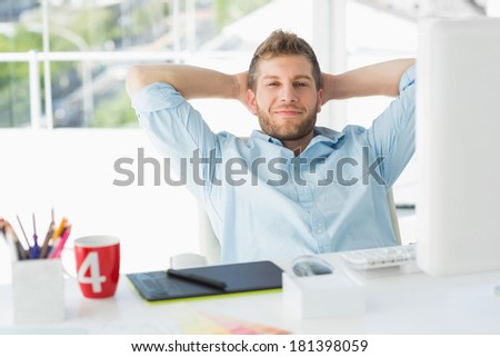 Designer relaxing at his desk smiling at camera in creative office - stock photo