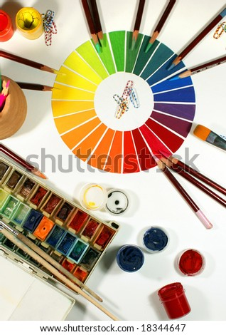 designer's work place with colored pencils, brushes and paints - stock photo