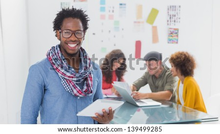Designer standing and smiling with his tablet in creative office - stock photo