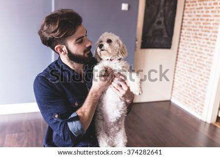 Designer taking a break from work and playing with his puppy - stock photo
