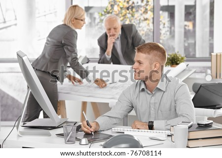 Designer team at work in office, young architect sitting at desk with drawing pad, older colleagues working on architectural plan.? - stock photo