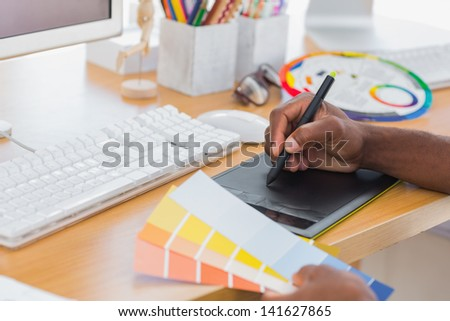 Designer using graphics tablet while holding colour charts - stock photo